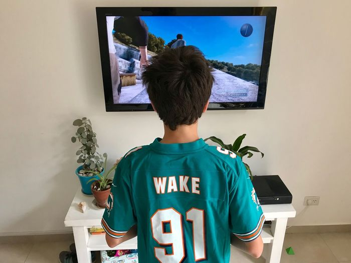 Boy playing XboxOne Xbox360 Xbox Rear View Indoors  One Person Leisure Activity Lifestyles Real People Waist Up Hair Clothing Portrait Young Adult Casual Clothing Standing Sport Home Interior Hairstyle Representation Day