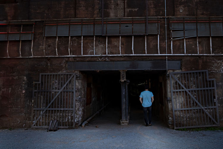 Rear view of man walking in old building