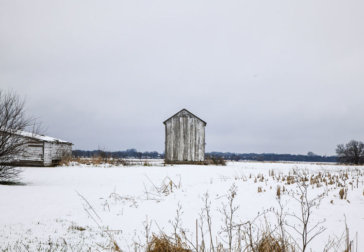 Barn on field by buildings against sky during winter