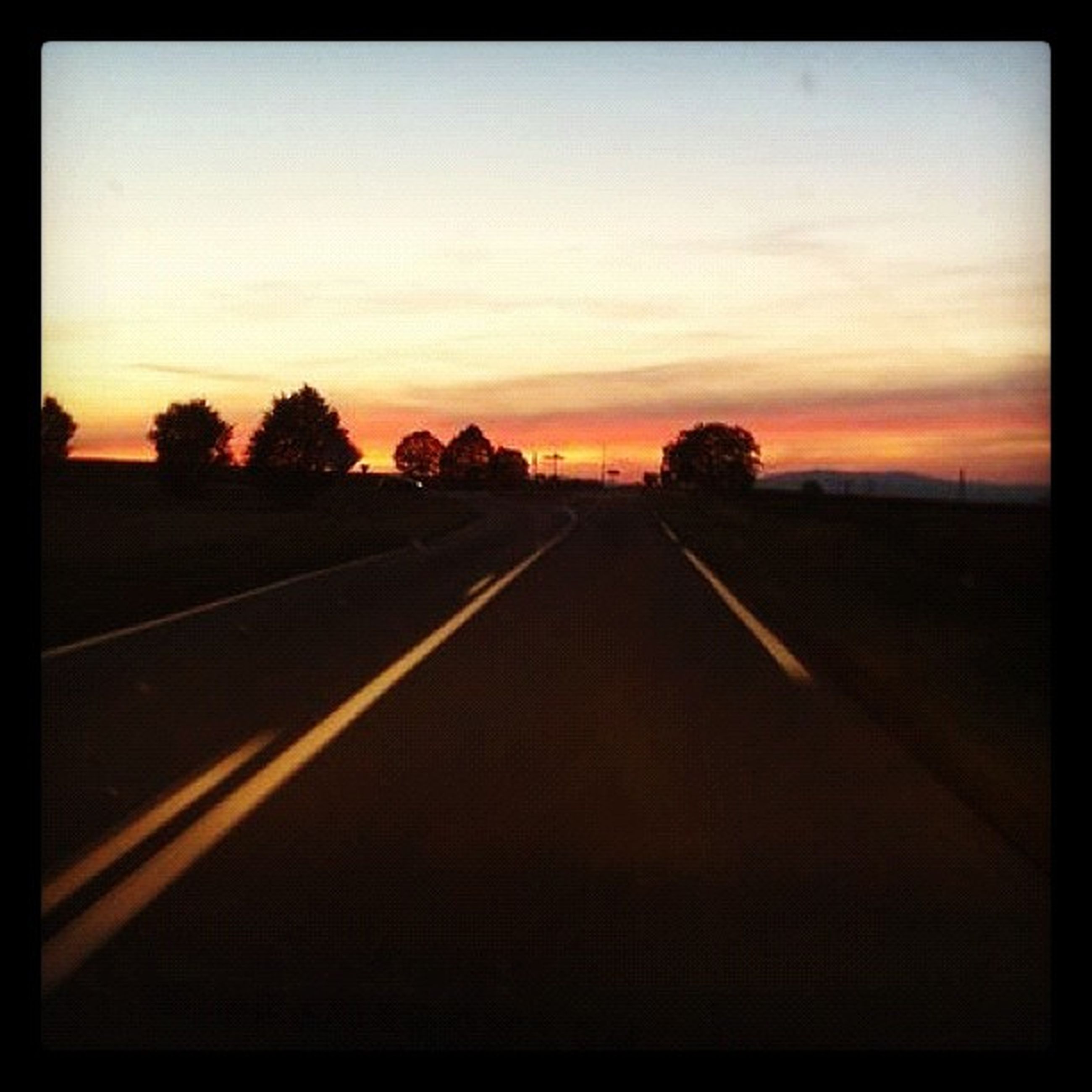 sunset, the way forward, transfer print, sky, transportation, diminishing perspective, orange color, auto post production filter, vanishing point, road, tranquil scene, tranquility, tree, landscape, silhouette, nature, empty, scenics, beauty in nature, dusk