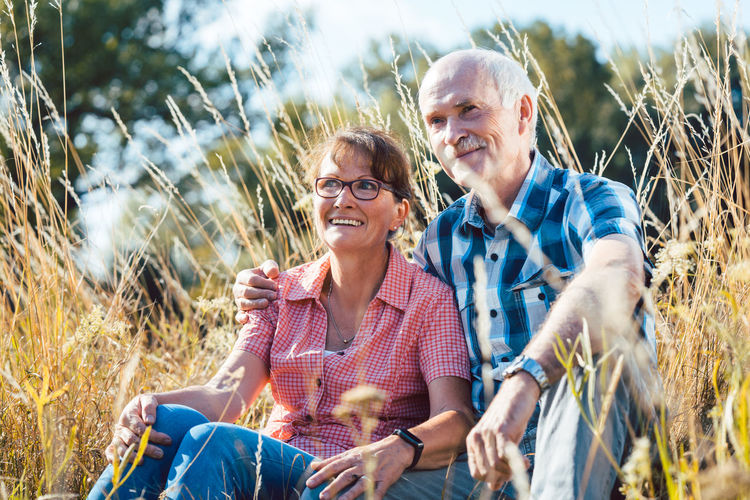 Senior couple enjoying some time together outdoors Couple Grass Man Nature Relaxing Woman Bonding Emotion Enjoying Life Field Happiness Meadow Old Love Outdoors Positive Emotion Senior Adult Seniors Sitting Smiling Summer Two People Women