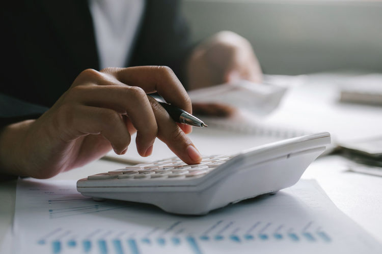 Close up of businessman or accountant hand holding pen working on calculator to calculate business