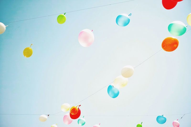 Low angle view of multi colored balloons hanging on rope against clear sky