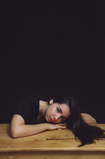 Portrait Of Young Woman Relaxing On Wooden Bench Against Black Wall At Home