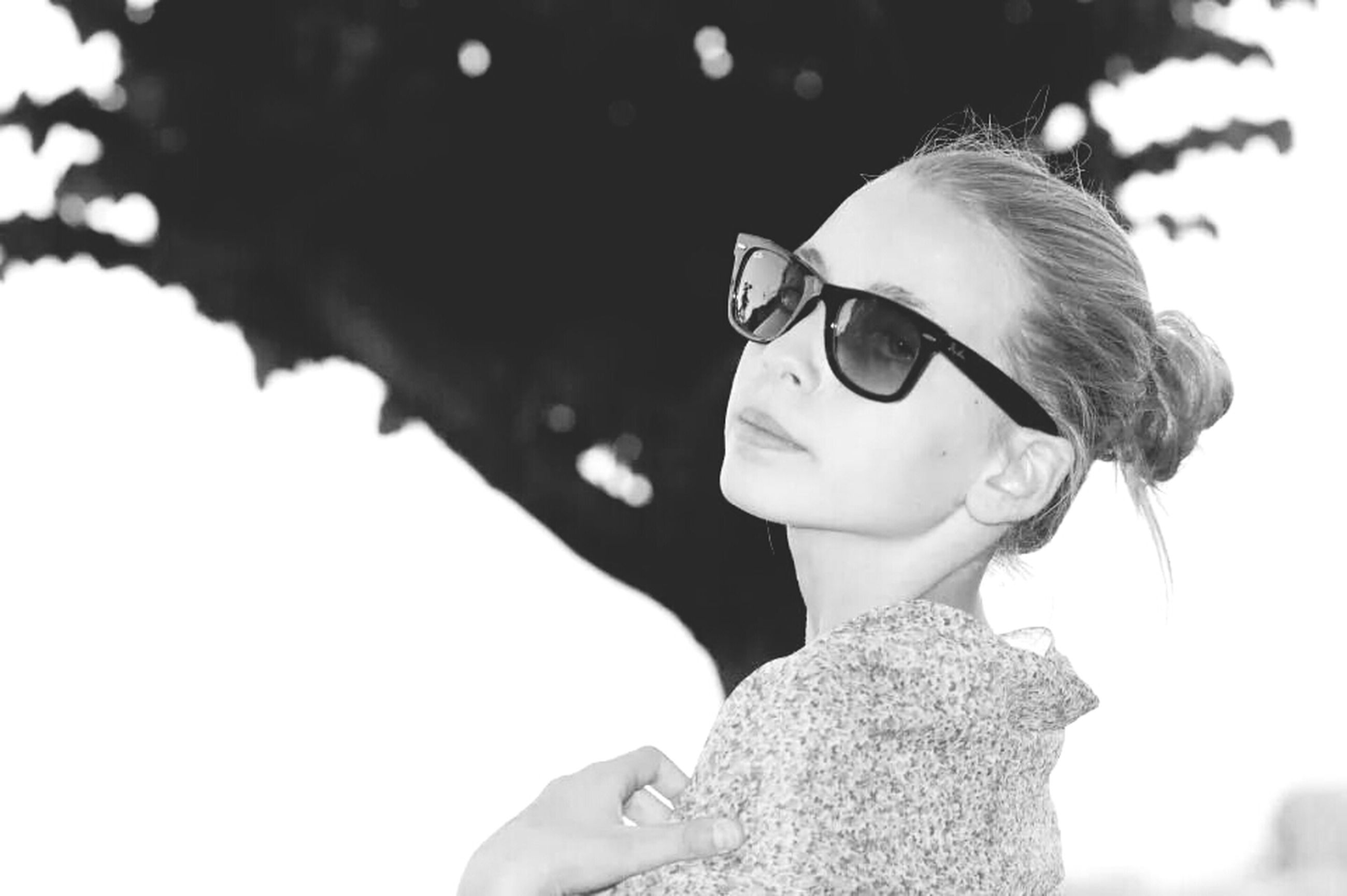 headshot, lifestyles, person, young adult, leisure activity, focus on foreground, sunglasses, portrait, looking at camera, head and shoulders, front view, casual clothing, close-up, holding, waist up, young women, smiling, human face