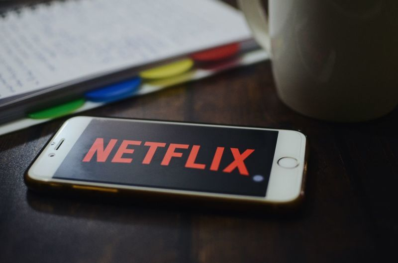 Netflix showing on iphone 6. Netflix Communication Text Western Script Technology Indoors  Close-up Table No People Wireless Technology Connection Computer Education Computer Equipment Still Life Laptop Book High Angle View Sign Information Selective Focus