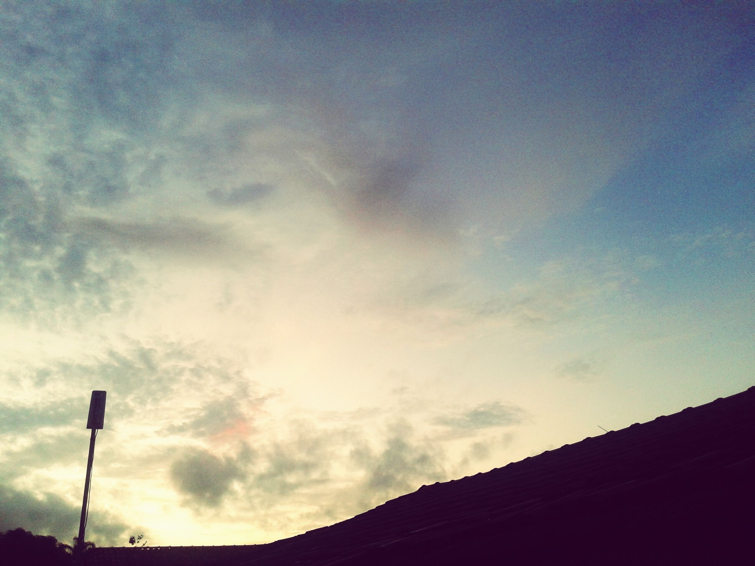 low angle view, sky, built structure, architecture, silhouette, building exterior, cloud - sky, street light, high section, cloud, cloudy, dusk, outdoors, sunset, no people, nature, lighting equipment, building, blue, house