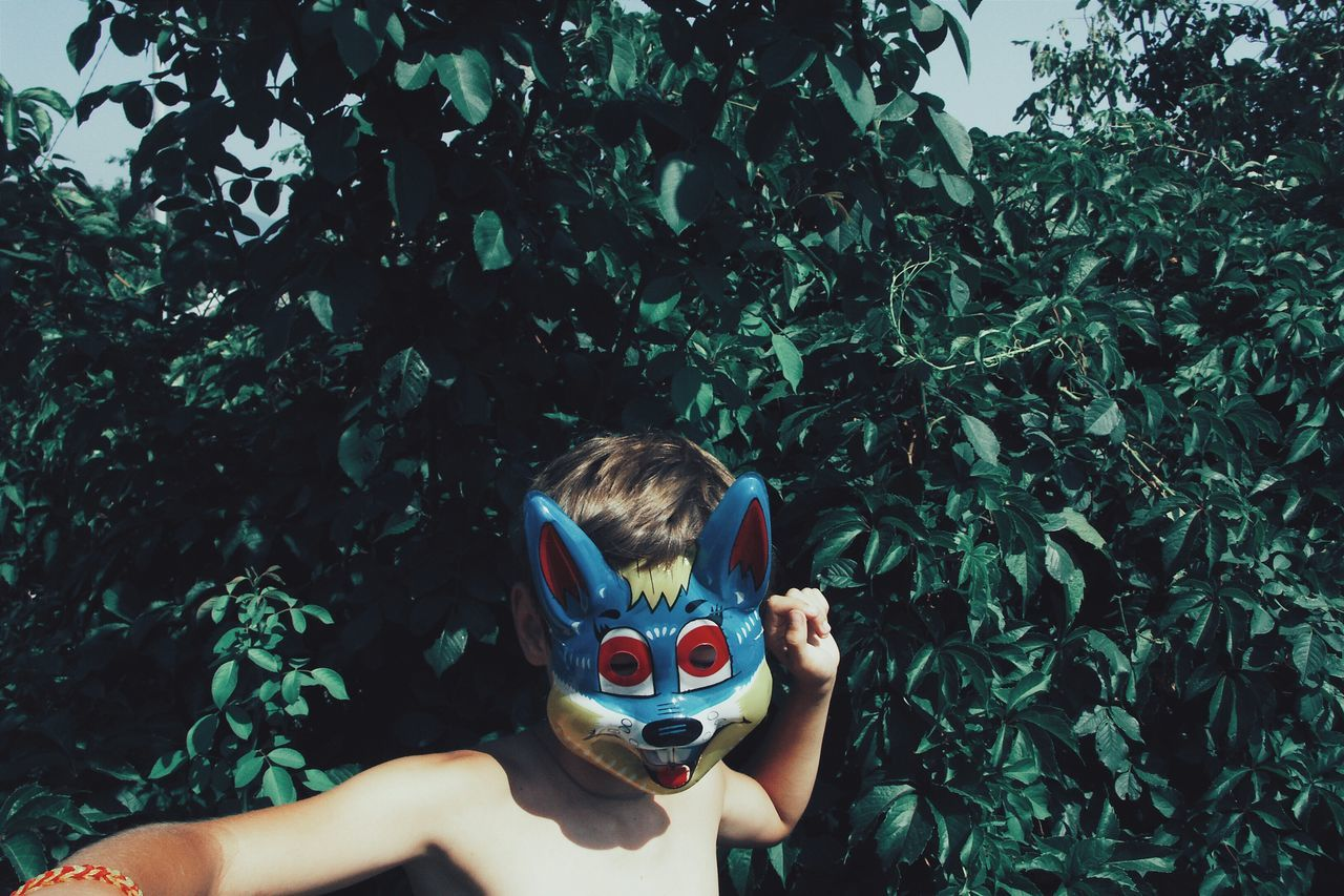 Shirtless boy wearing mask against plants