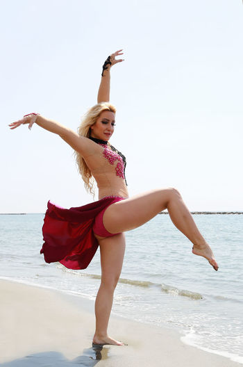 Side view of woman with arms raised dancing at beach against clear sky
