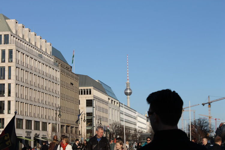 People walking on street by buildings and fernsehturm against blue sky