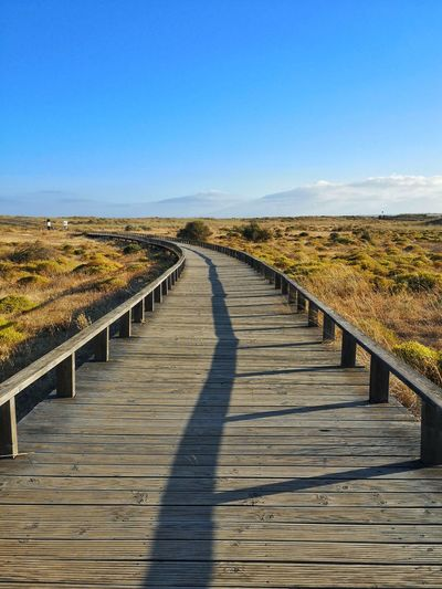 View of wooden boardwalk against clear blue sky