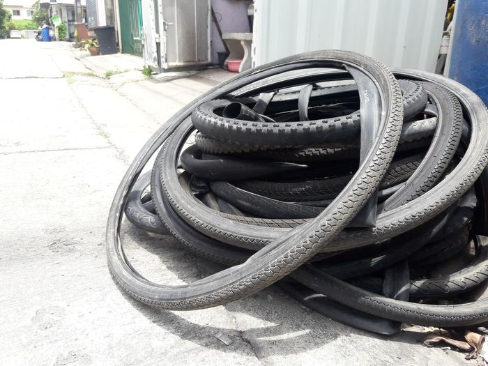 Old bicycle tire Garage Repairman 0LD Tire Bicycle Stack Rubber Black Dirty Daytime Cycle Spare Parts Change Tires Deteriorate Building Exterior Close-up Built Structure Architecture