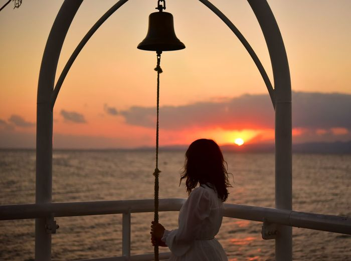 Rear view of woman standing by railing against sea during sunset