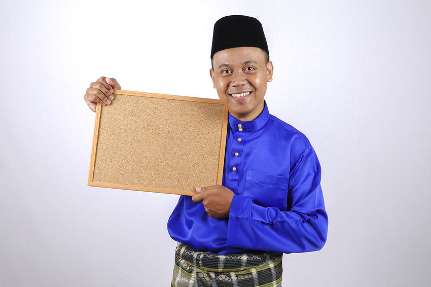 YOUNG SMILING ASIAN MODEL SMILING HOLDING CHALK BOARD Baju Melayu Eid Mubarak Hari Raya Aidilfitri Angpow Cheerful Confidence  Copy Space Emotion Front View Happiness Holding Indoors  Looking At Camera Money Packet One Person Portrait Smiling Standing Studio Shot Teeth Toothy Smile Waist Up White Background Young Adult