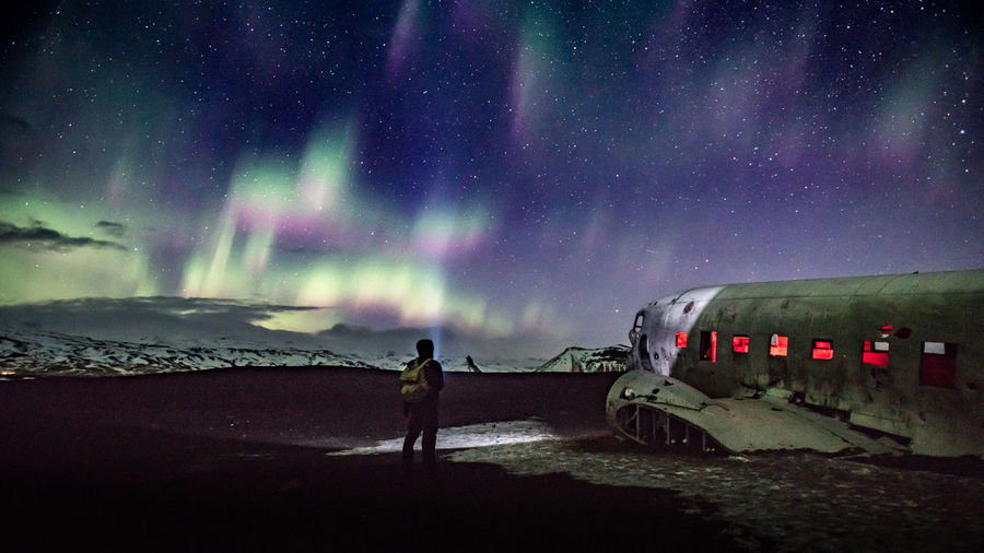 Rear view of man looking at abandoned ship in sea against sky during night
