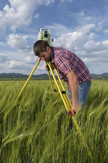 Land surveyor and his equipment Agriculture Daytime Industry Station Sunny Wheat Working Clouds Engineer Engineering Equipment Geodesy Internet Landsurveyor Location Measurement Network One Man Only Point Professional Occupation Spring Summer Technology Total Wireless Technology