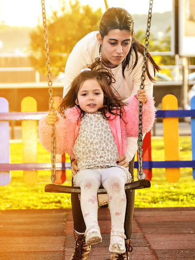 Adult Bonding Child Childhood Daughter Day Females Full Length Girls Outdoor Play Equipment Outdoors Park - Man Made Space People Playground Preschool Real People Sitting Swing Togetherness Two People Young Adult First Eyeem Photo