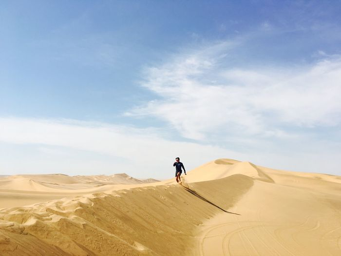 Young man running on desert against sky
