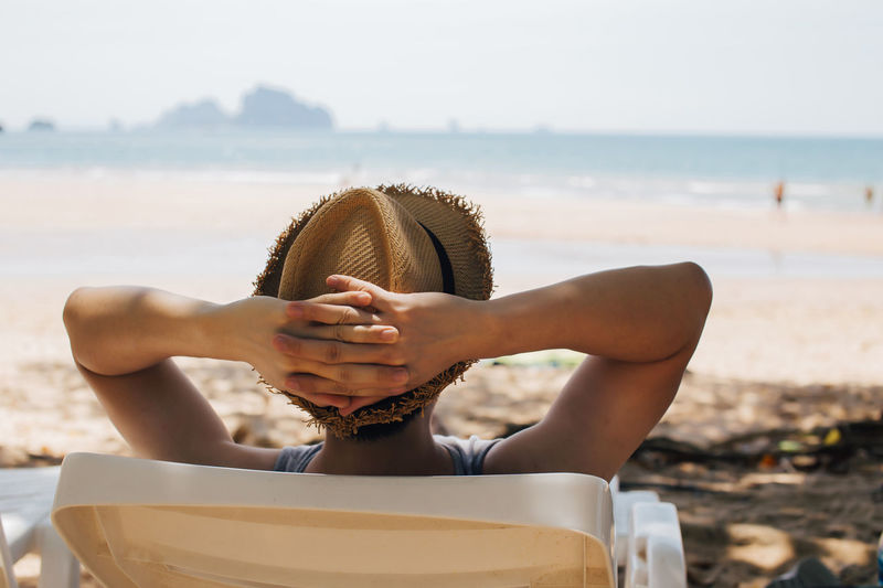 Close-up of young male traveler relaxing and sitting on beach chair - summer vacation concept Water Sea Beach One Person Land Leisure Activity Real People Nature Relaxation Day Lifestyles Focus On Foreground Sky Women Adult Sunlight Beauty In Nature Hat Outdoors Retirement Comfortable Resting Resting Time Summertime Relaxing Moments