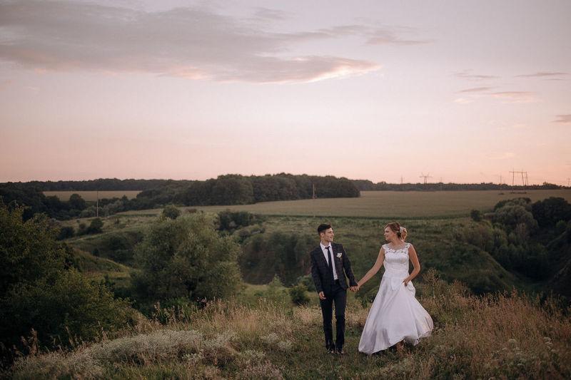 Full length of newlywed couple walking on grassy field