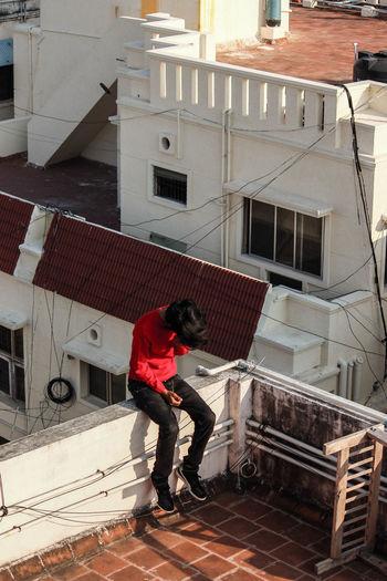 Full length of man standing by railing against buildings