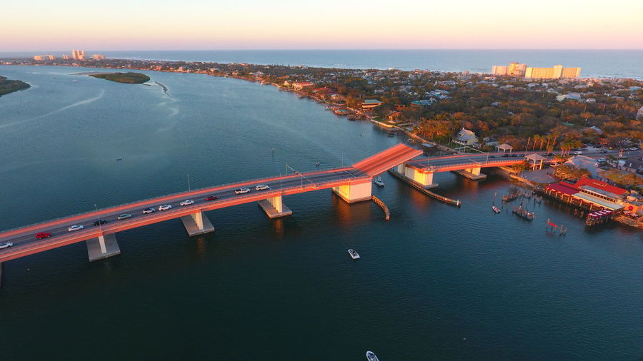 Aerial view of bridge over river against sky at sunset