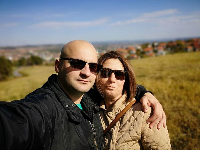 Portrait of couple wearing sunglasses against sky