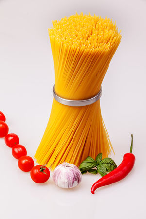 Spaghetti standing with fresh spices and vegetables, raw on gray background, Basil Dinner Freshness Garlic Spaghetti Cherry Tomatoes Chilli Close-up Food Food And Drink Freshness Garlic Healthy Eating Indoors  Ingredient Italian Food No People Pasta Raw Food Red Studio Shot Tomatoes Vegetable White Background Yellow