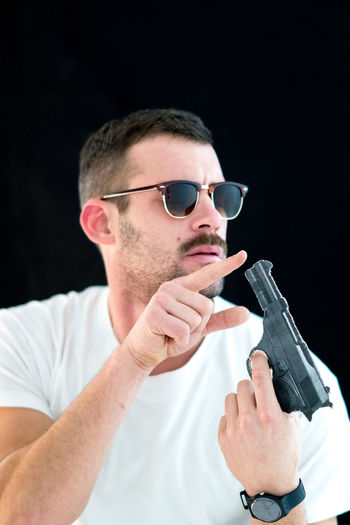 Man touching gun against black background