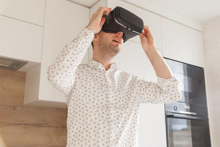 Man wearing virtual reality simulator at home