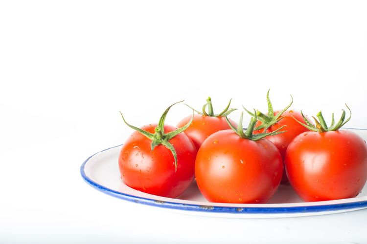 Close-up of tomatoes in plate against white background