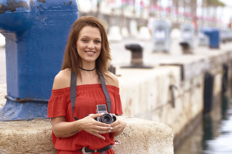 Portrait of smiling young woman holding camera while using phone outdoors