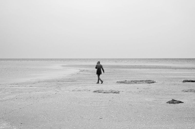Rear view of woman walking at beach against clear sky