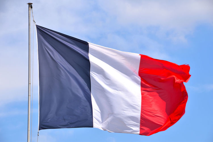 Low angle view of french flag waving sky during sunny day