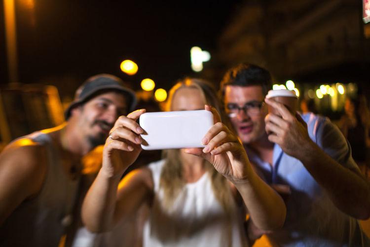Cheerful friends taking selfie at night