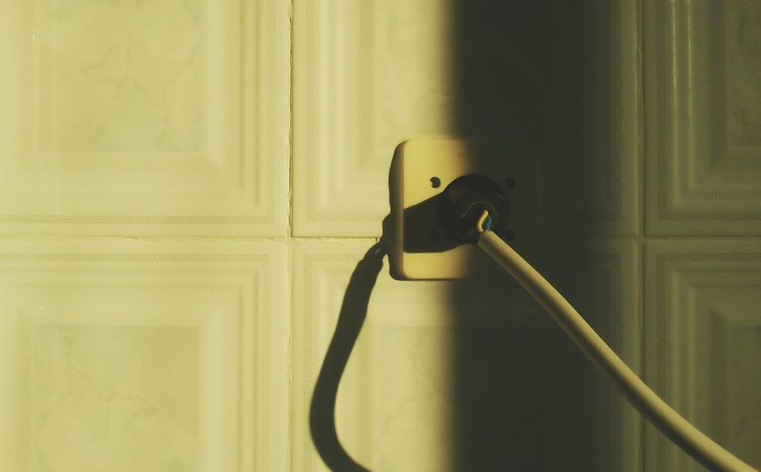 Close-up of cable in outlet on wall