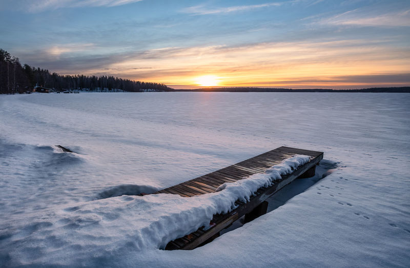 Scenic winter landscape with pier and sunset at evening light in Finland Sunset Sky Water Cold Temperature Winter Beauty In Nature Scenics - Nature Snow Tranquil Scene Nature Tranquility Cloud - Sky Idyllic Frozen No People Non-urban Scene Sun Orange Color Ice Cold Finland Lake Plant Tranquility Atmospheric Mood
