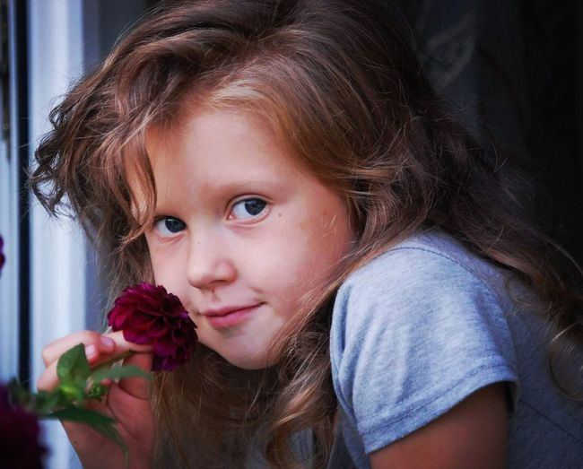 Close-Up Portrait Of Smiling Girl Holding Flower At Home