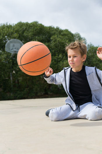 Boy playing with basketball at park