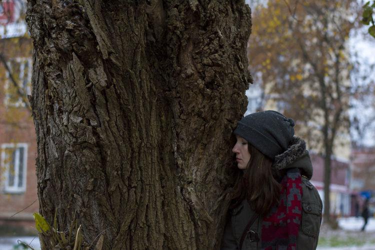 Woman near a tree trunk