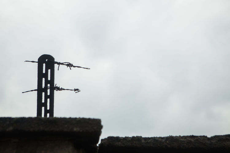 Low angle view of weather vane on field against sky