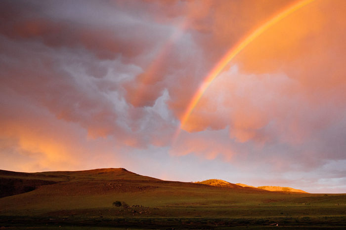 SCENIC VIEW OF RAINBOW OVER LAND AGAINST SKY DURING SUNSET