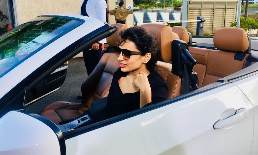 Woman Wearing Sunglasses While Sitting In Convertible Car