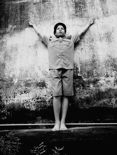 Low angle view of boy wearing police uniform while standing against weathered wall