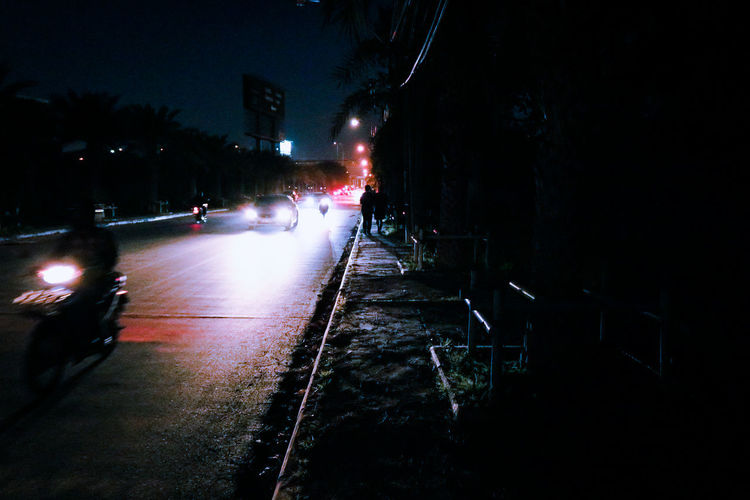 Cars on illuminated street in city at night