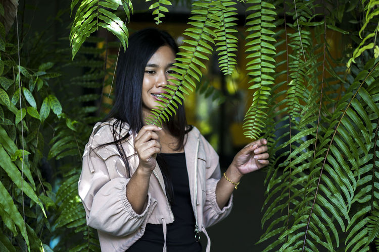 Young woman standing against plants