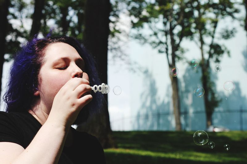Mid shot of woman blowing bubbles EyeEm Selects One Person Real People Lifestyles Bubble Plant Headshot Bubble Wand Blowing Young Adult Portrait Focus On Foreground Leisure Activity Nature Women Holding Young Women Tree Adult Outdoors