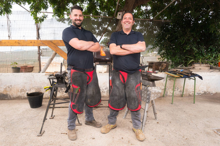 Portrait of smiling blacksmiths standing at workshop