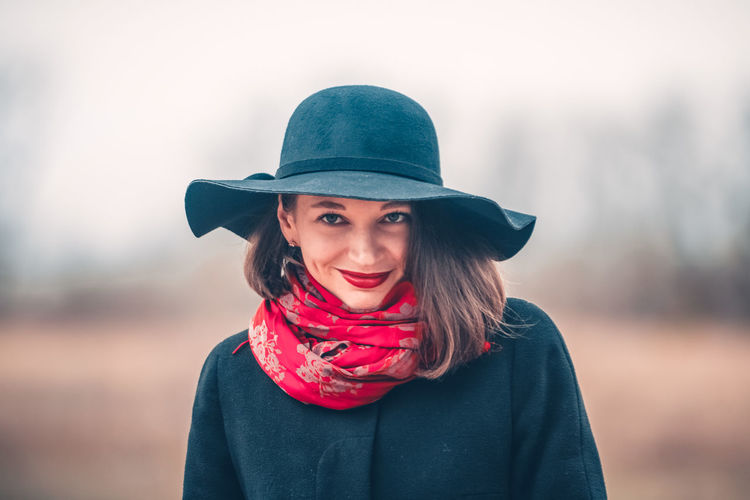 Portrait of woman wearing hat and red scarf against sky