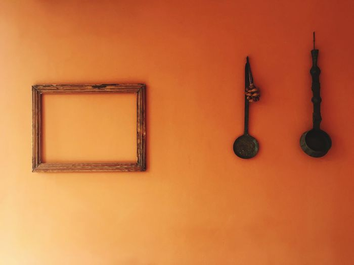 Empty picture frame and kitchen utensils on orange wall